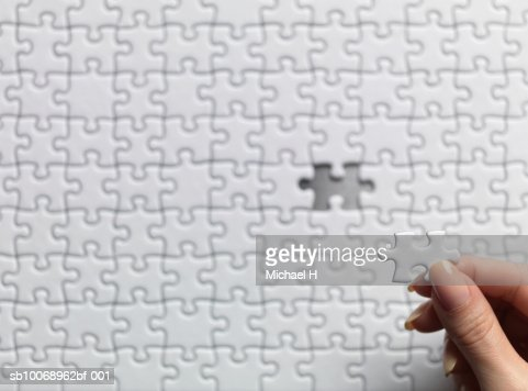 Woman holding one jigsaw piece over puzzle : Stock Photo
