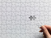 Woman holding one jigsaw piece over puzzle