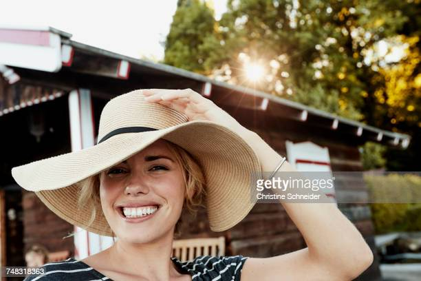 Woman holding onto wide-brimmed hat
