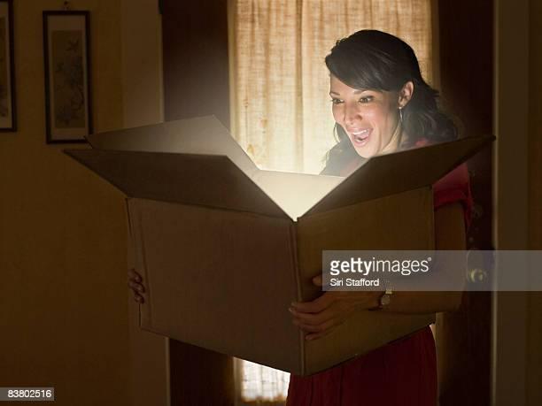 Femme tenant ouvrir la boîte avec la lumière illuminant les