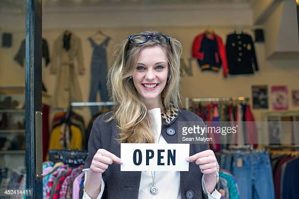 Woman holding open sign in clothes shop