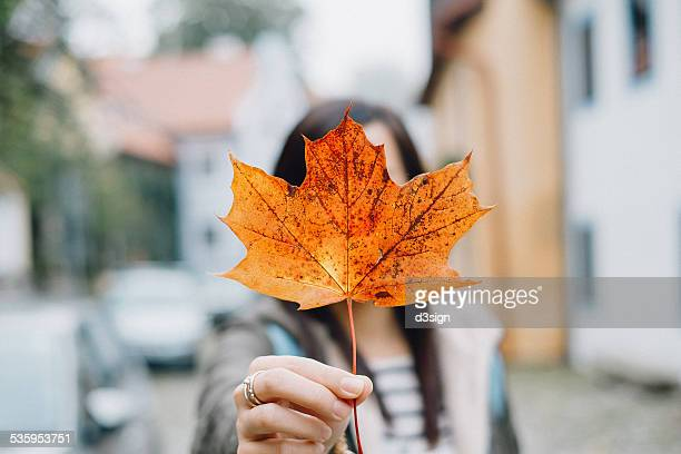 Woman holding orange-red maple leaf over her face