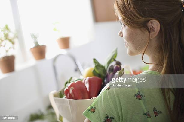 Woman holding organic vegetables in canvas bag