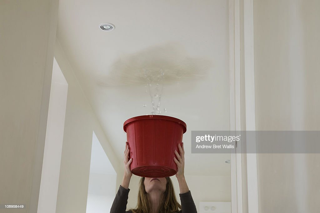 woman holding out a bucket to stop a roof leak : Stock Photo