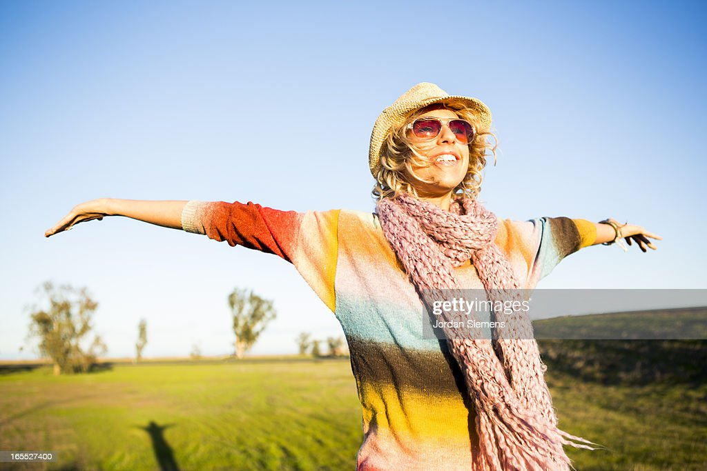 A woman holding out her arms in a field. : Stock Photo
