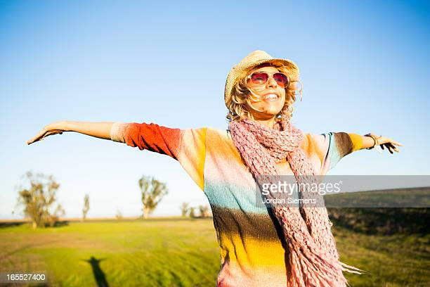 A woman holding out her arms in a field.