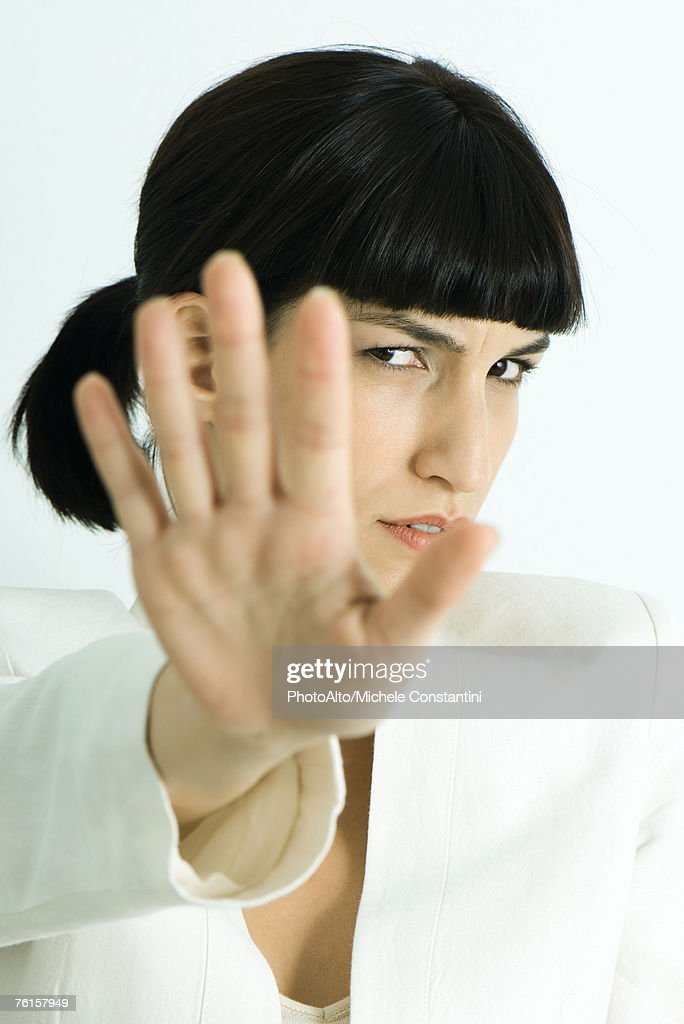 'Woman holding out palm of hand to camera, scowling, head and shoulders, portrait' : Stock Photo