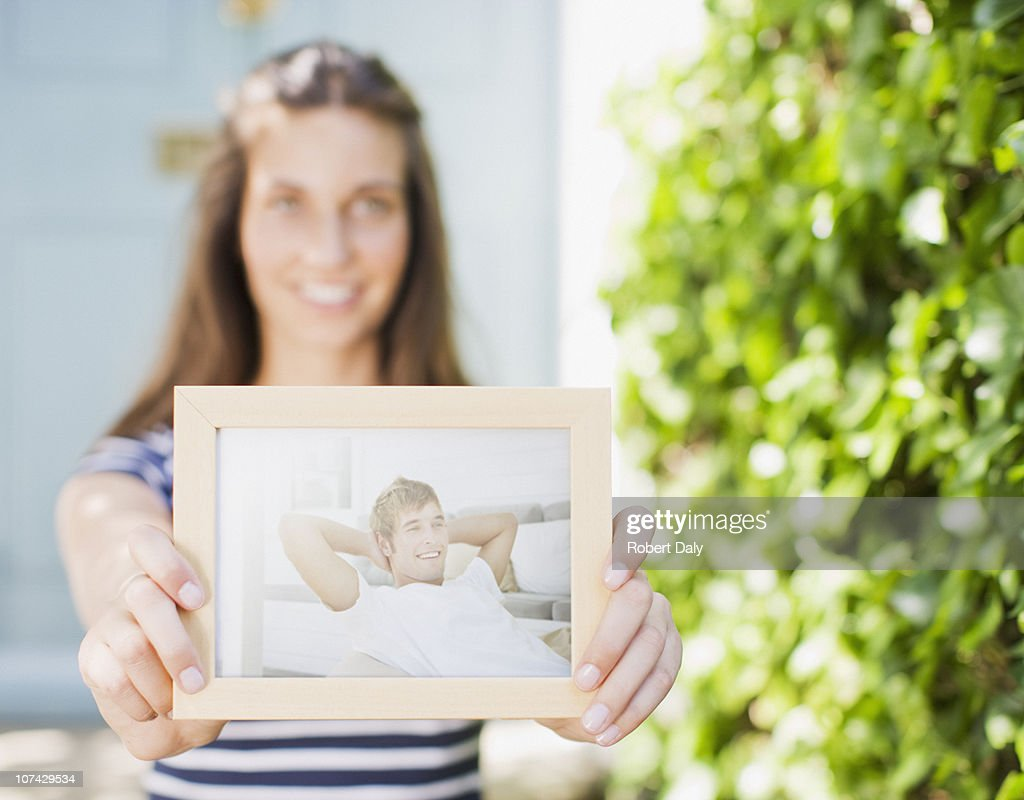 Woman holding out photograph of boyfriend : Stock Photo