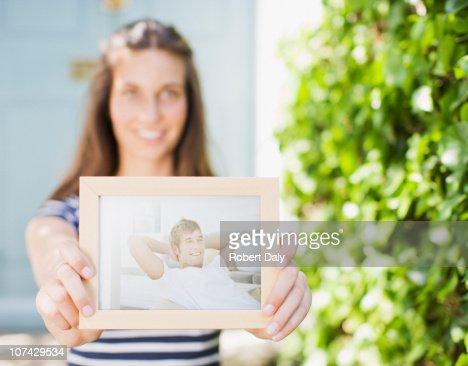 Woman holding out photograph of boyfriend : Bildbanksbilder
