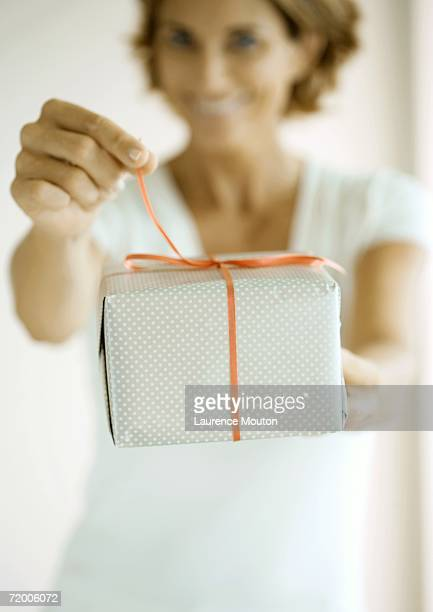 Woman holding out present, pulling on ribbon