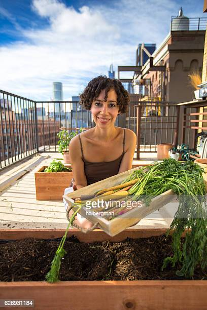 Woman Holding Out Tray of Carrots in Urban Rooftop Garden
