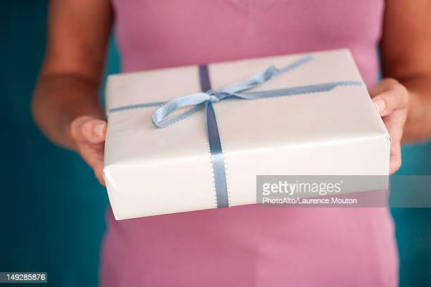 Woman holding out wrapped gift, cropped