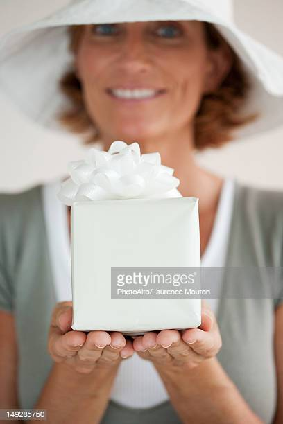 Woman holding out wrapped gift