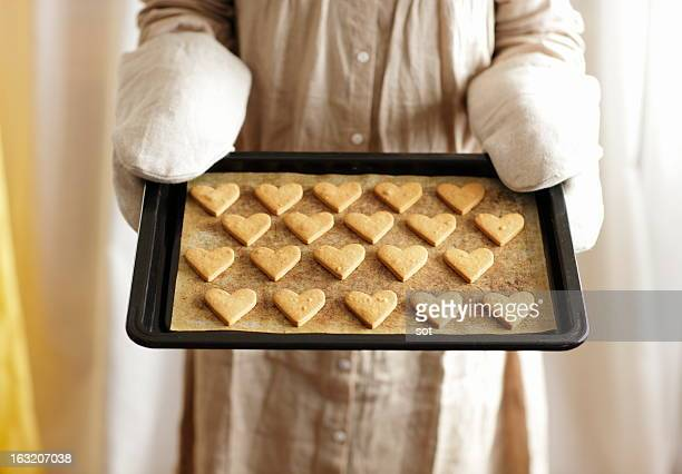 Woman holding oven tray of heart cookies