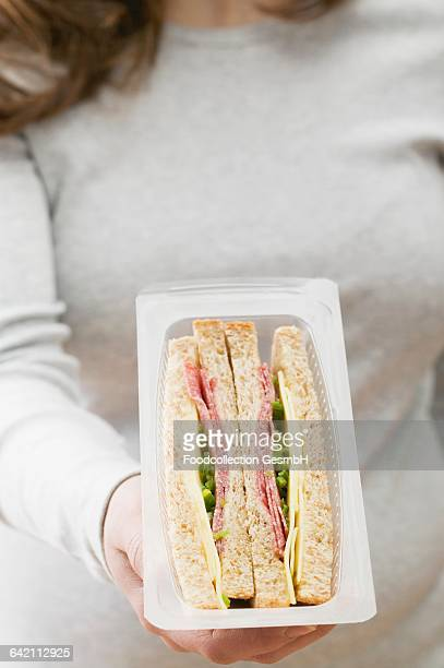 Woman holding pack of sandwiches