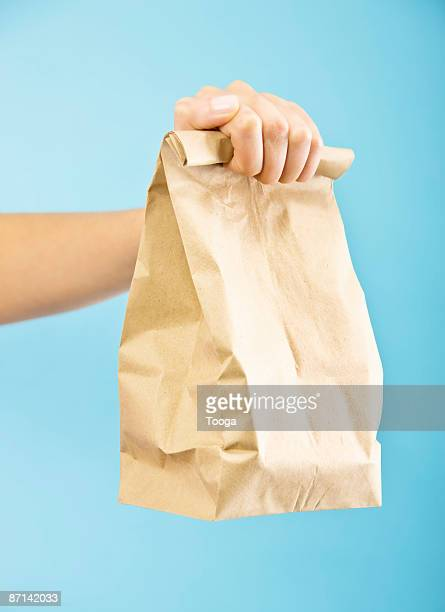 Woman holding packed brown bag lunch