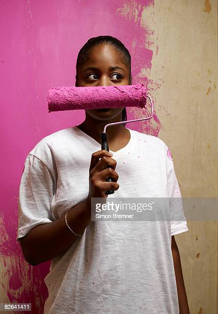 Woman holding paint roller across face