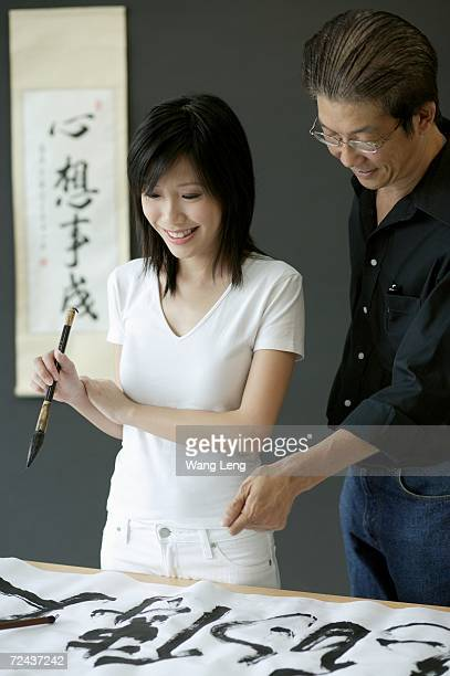 Woman holding paintbrush, looking at Chinese painting, man standing next to her