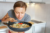 oung woman going to eat rice with vegetables, smelling delicious aroma fro just prepared food