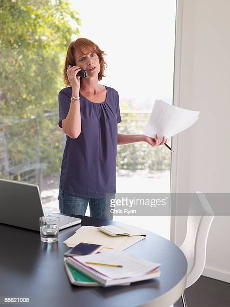 Woman holding papers and talking on cell phone
