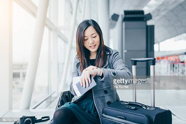 Woman holding passport checking time at airport