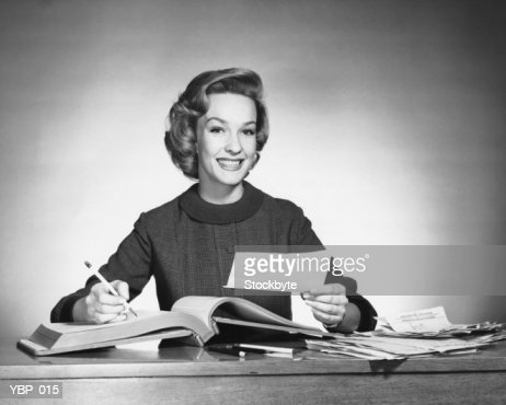 Woman holding pencil and paper, open book in front of her