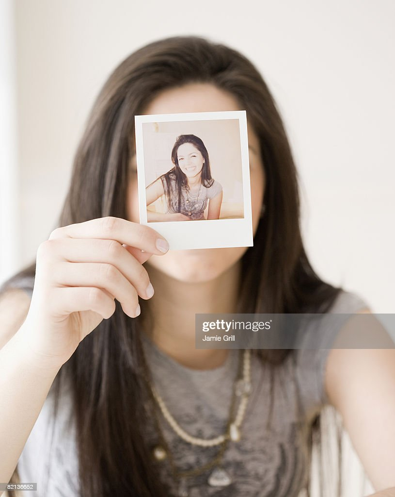 Woman holding photograph in front of face