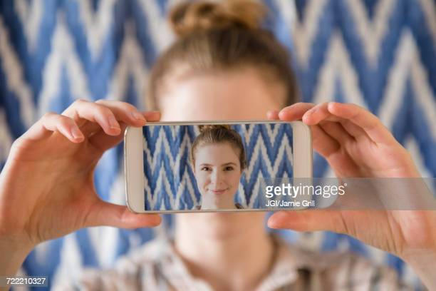 Woman holding photograph of cell phone selfie in front of face