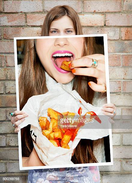 woman holding picture of bag of chips