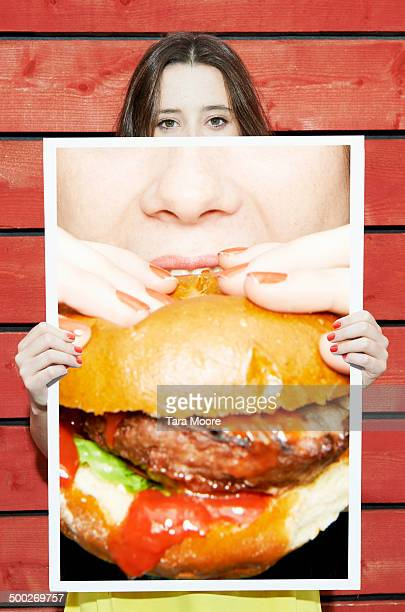 woman holding picture of hamburger