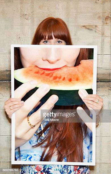 woman holding picture of watermelon