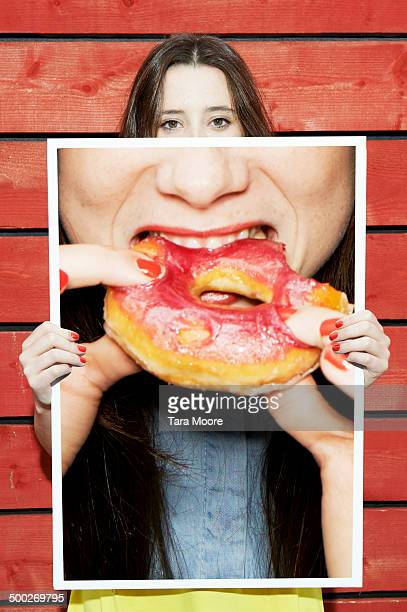woman holding picture of woman eating donut