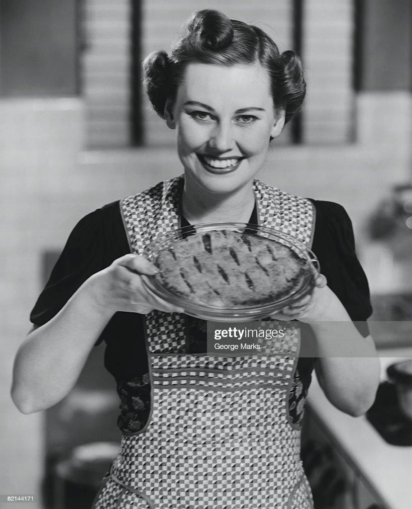 Woman holding pie, (B&W), portrait
