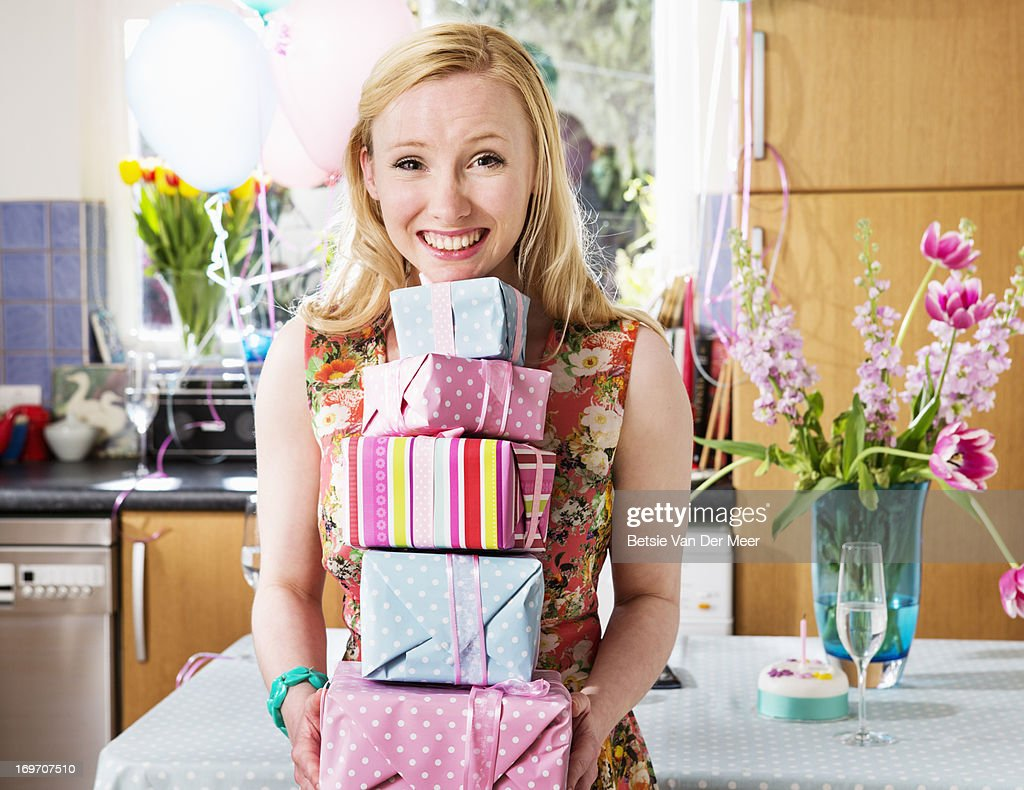 Woman holding pile of presents, smiling. : Stock Photo