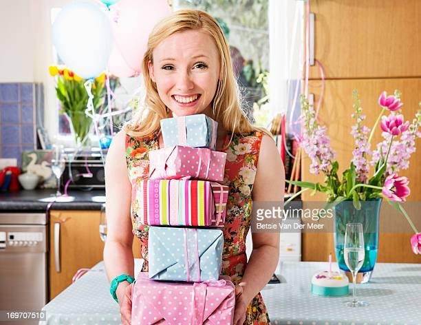 Woman holding pile of presents, smiling.