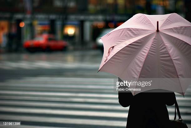 Woman holding pinkie wrinkles umbrella