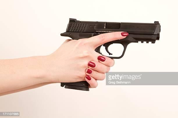 Woman holding pistol, finger off trigger