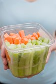 Woman holding plastic container of celery and carrots