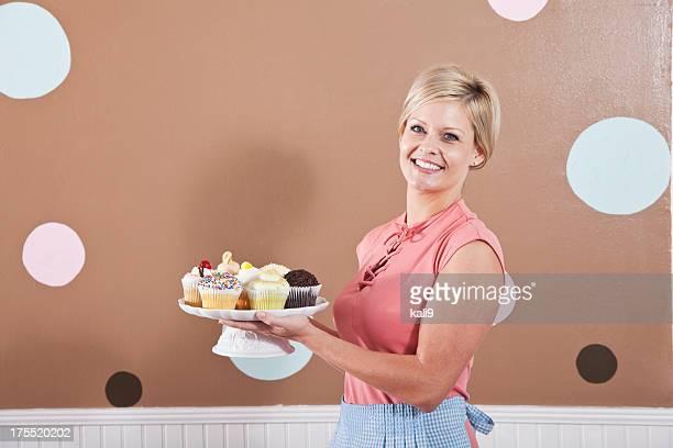 Frau hält Teller mit cupcakes