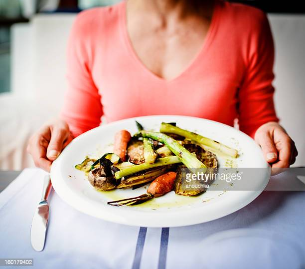 Woman holding plate of grilled vegetables in a restaurant