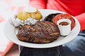 Woman holding plate of steak, baked potato, vegetables & sauce