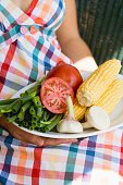 Woman holding plate of vegetables & corn on the cob for grilling