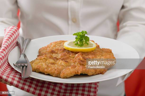 Woman holding plate of Wiener schnitzel, close up