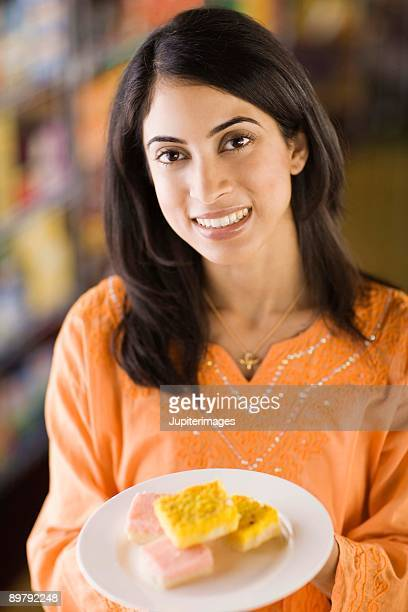 Woman holding plate of with pastries