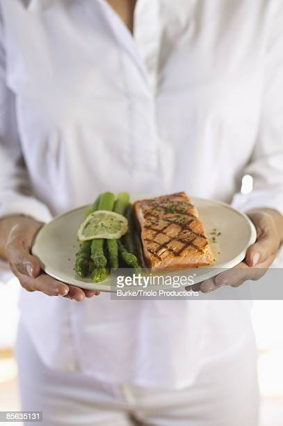 Woman holding plate with salmon and asparagus
