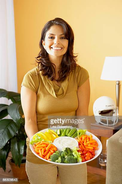 Woman holding platter of vegetables