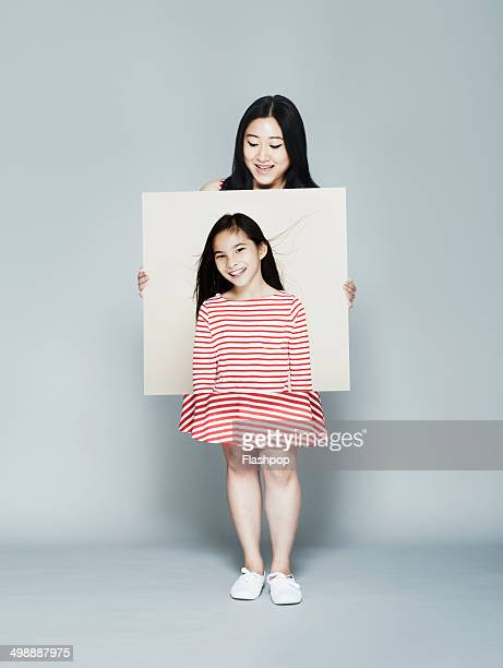 Woman holding portrait of herself as a child
