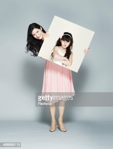 Woman holding portrait of herself as a child : Foto de stock