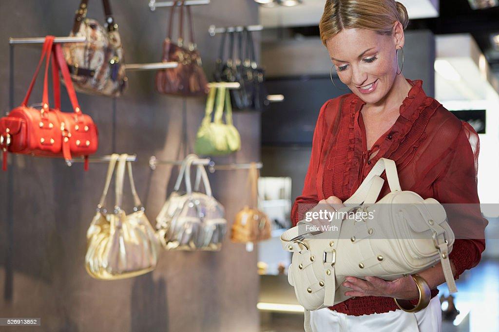 Woman holding purse in boutique : Foto de stock