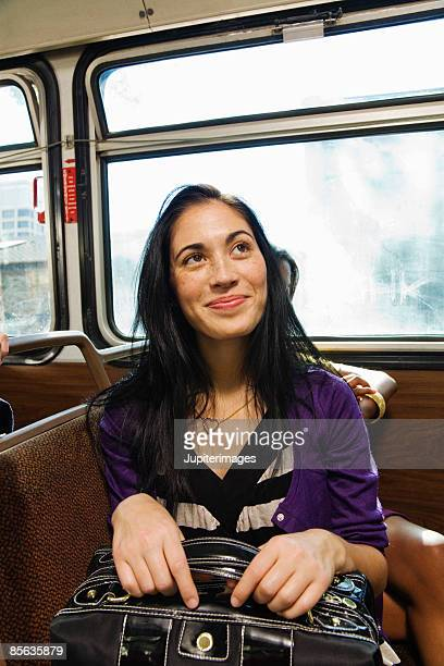 Woman holding purse riding bus